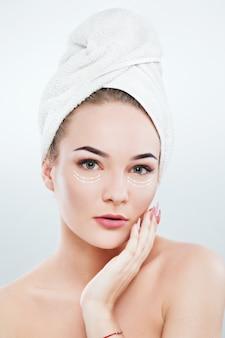 Bella donna con le sopracciglia scure e le spalle nude, indossa un asciugamano bianco sulla testa che tiene la mano con il manicure rosa