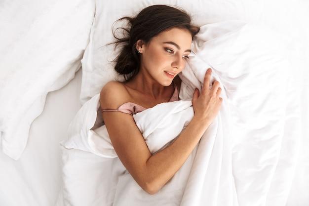 Bella donna con i capelli scuri sorridente, mentre giaceva e dorme nel letto su lino bianco