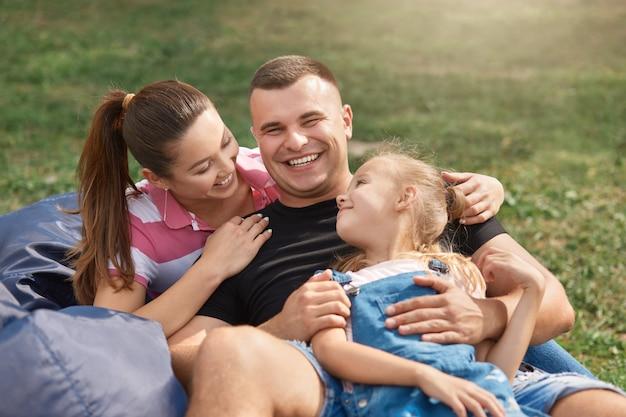 Bella donna con la figlia e il marito seduto sulla sedia frameless blu nel parco e godendo di trascorrere del tempo insieme all'aperto