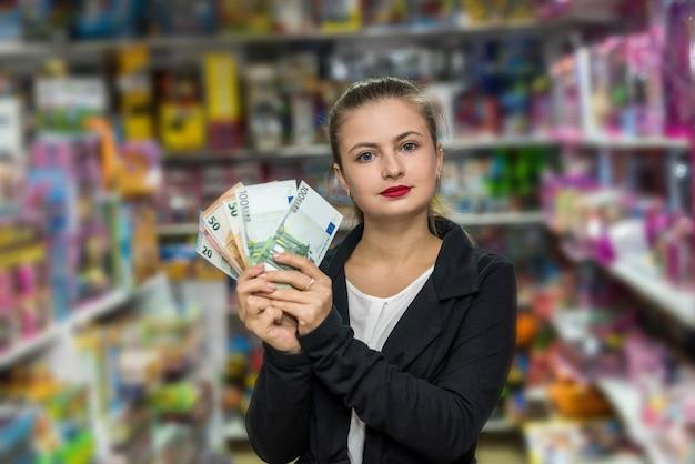 Bella donna con banconote in dollari in posa nel negozio di giocattoli