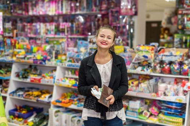 Bella donna con euro in posa nel negozio di giocattoli