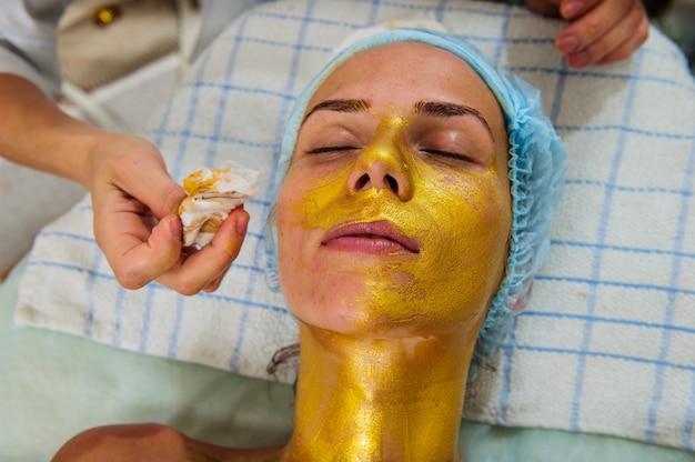 Bella donna con maschera d'oro facciale al salone di bellezza