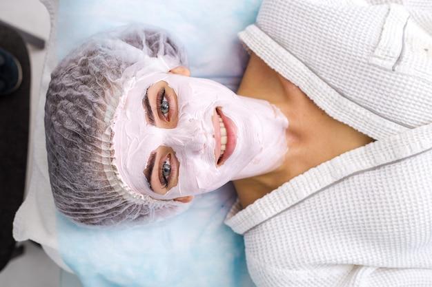 Bella donna con maschera facciale al salone di bellezza