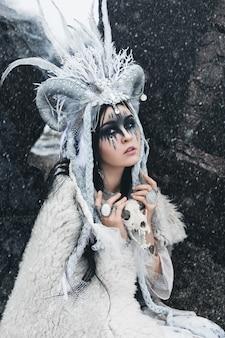 Bella donna con trucco di fantasia e in una corona seduta nella neve che cade