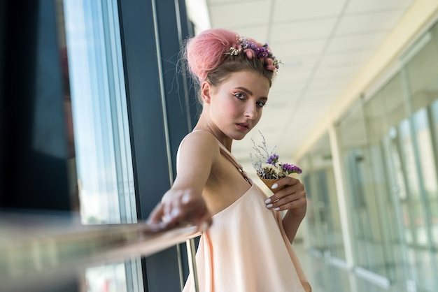 Bella donna con il trucco fresco in posa vicino alla finestra con fiori