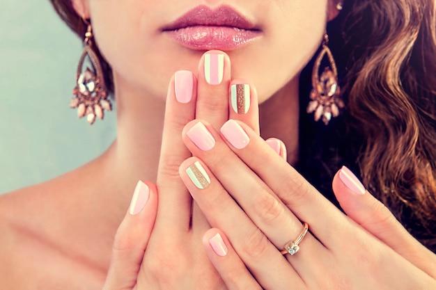 Bella donna con manicure fresca e trucco che indossa gioielli