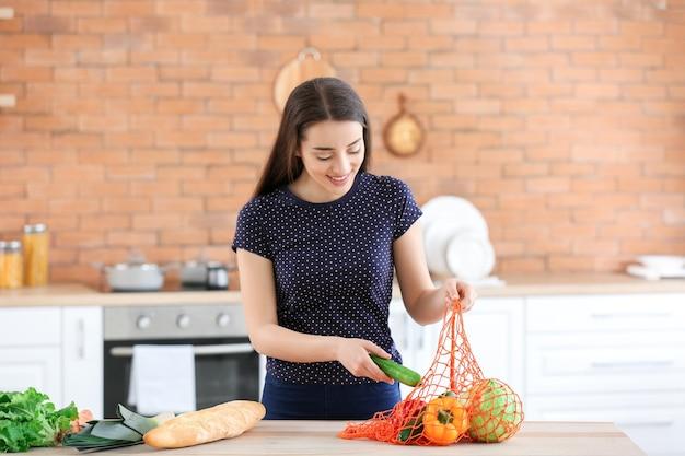 Bella donna con prodotti freschi in cucina a casa