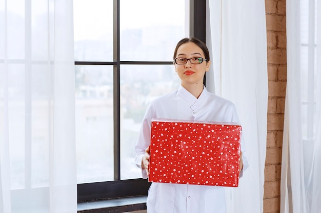 Bella donna con gli occhiali in camice da laboratorio che tiene grande scatola regalo vicino alla finestra.