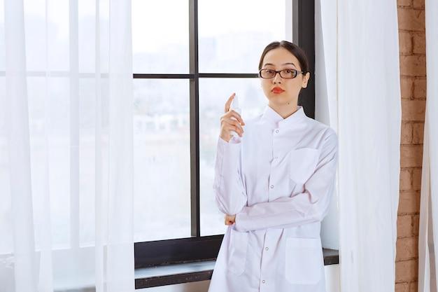Bella donna con gli occhiali in camice da laboratorio che tiene disinfettante spray vicino alla finestra.