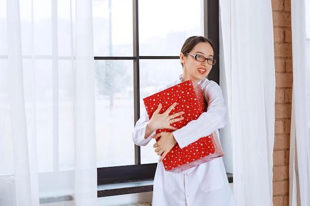 Bella donna con gli occhiali in camice da laboratorio che abbraccia la grande scatola regalo vicino alla finestra.