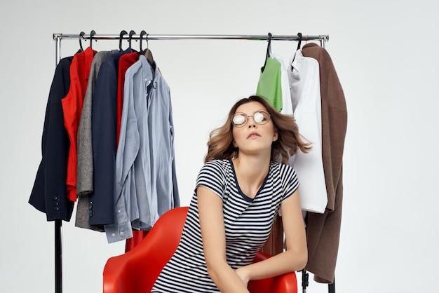 Bella donna con gli occhiali che provano sullo sfondo isolato shopaholic del negozio di abbigliamento