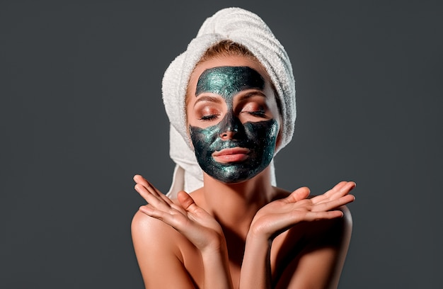 Bella donna con la maschera staccabile verde su una parete grigia.