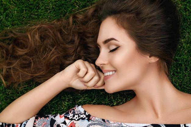 La bella donna con i capelli ricci sani sta trovandosi sull'erba