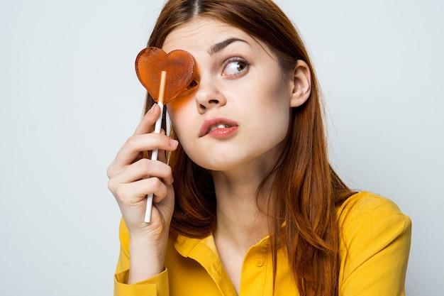 Bella donna con un lecca-lecca di cuore in una camicia gialla pone emozioni diverse san valentino