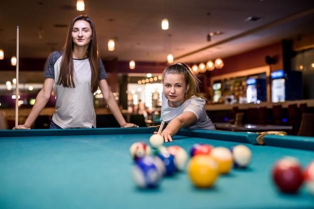 Bella donna con la sua amica che gioca a biliardo nel pub