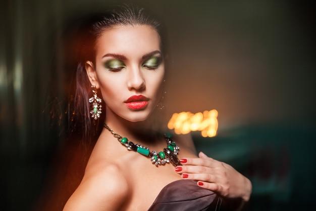 Bella donna con gioielli sopra il buio