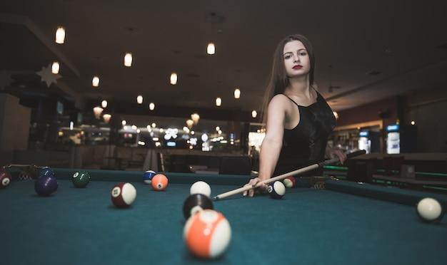 Bella donna con i capelli lunghi che giocano a biliardo
