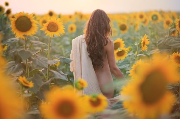 Bella donna con i capelli lunghi sexy indietro in un campo di girasoli in estate alla luce del sole
