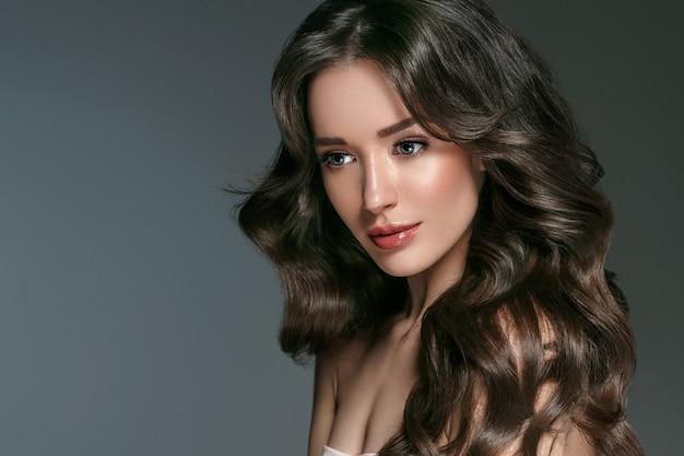 Bella donna con capelli lunghi, lucentezza e ricci, ragazza di bellezza femminile su sfondo grigio dar. colpo dello studio.