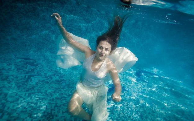 Bella donna con i capelli lunghi che nuota sott'acqua in piscina