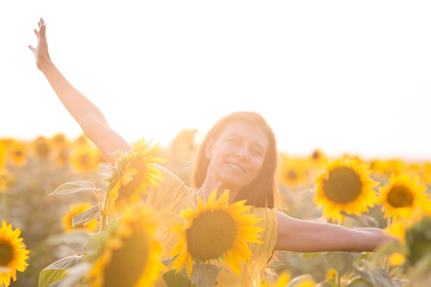 Bella donna con i capelli lunghi in abito bianco in un campo di girasoli in estate alla luce del sole