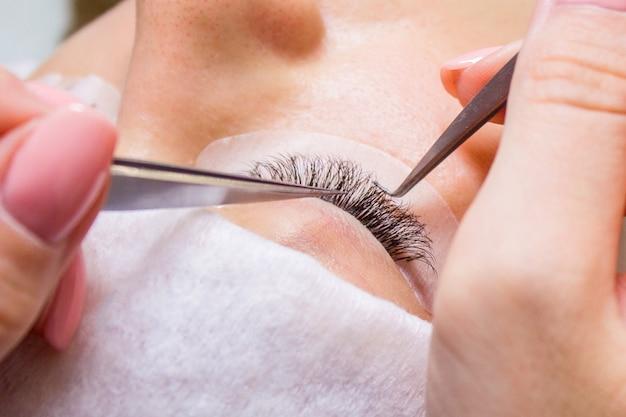 Bella donna con lunghe ciglia in un salone di bellezza. procedura di estensione ciglia.