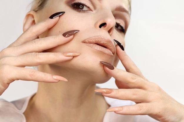 Bella donna con una lunga manicure ricoperta di sfumature naturali di smalto per unghie