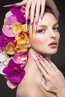 Bella donna con unghie lunghe, pelle perfetta, capelli di orchidee. ritratto girato in studio.
