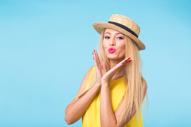 Bella donna con capelli biondi lunghi dritti. modello di moda in posa sulla parete blu con copyspace