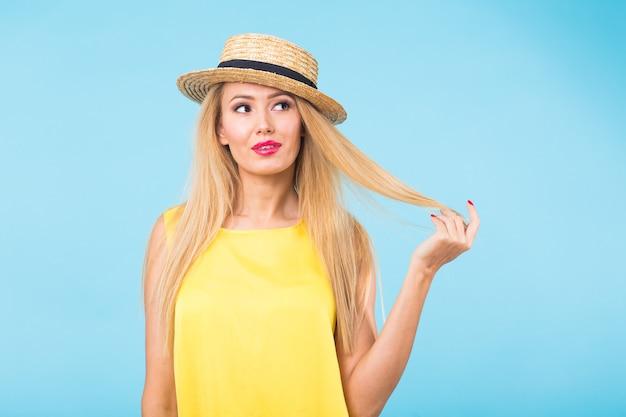 Bella donna con capelli biondi lunghi dritti. modello di moda in posa sulla parete blu