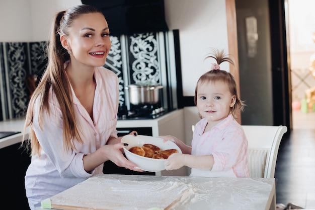 Bella donna con la ciotola adorabile della tenuta del bambino con i biscotti