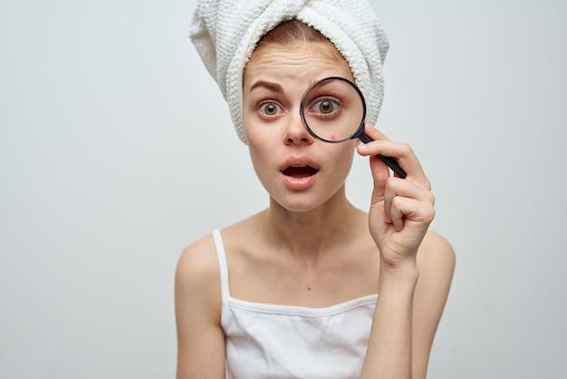 La bella donna con una lente d'ingrandimento a disposizione dermatologia ha isolato il fondo