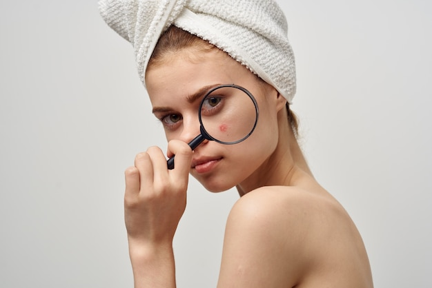 Bella donna con una lente d'ingrandimento in mano problemi di pelle