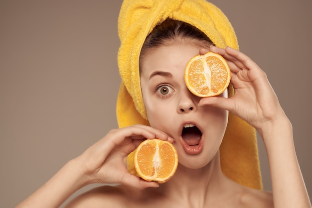 Bella donna con il mandarino di cura della pelle del corpo nudo in mano