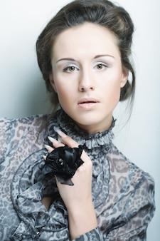 Bella donna con trucco naturale con la mano che porta grande anello del fiore.