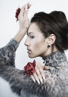 Bella donna con trucco naturale con mano che indossa un grande anello di fiori.