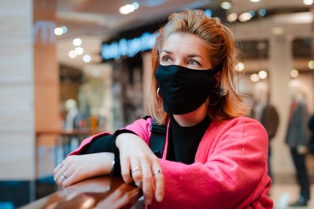 Bella donna con telefono cappotto rosa brillante shopping mall con maschera protettiva nera sul viso dall'aria infetta da virus.