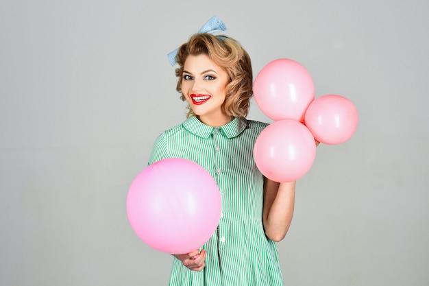 Bella donna con palloncini rosa sulla superficie grigia