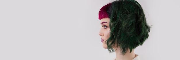 Bella donna con capelli colorati professionali viola verde occhi luminosi e trucco labbra lips