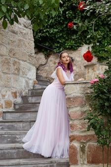 Bella donna con i capelli viola in un abito da sposa bianco cammina in giardino. trucco naturale