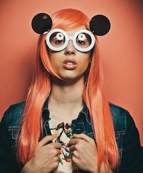 Bella donna con i capelli rossi che indossa grandi occhiali da sole Foto Premium
