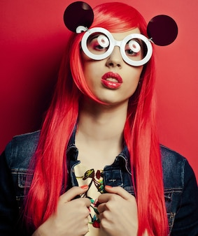 Bella donna con i capelli rossi che indossa grandi occhiali da sole