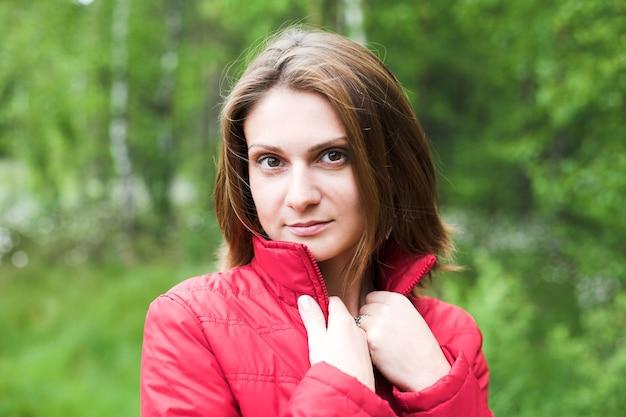 Bella donna con giacca rossa nel parco