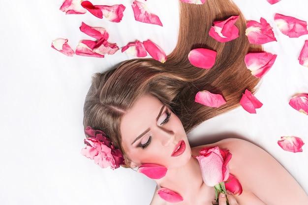 Bella donna con rose che giace tra i petali di rosa.
