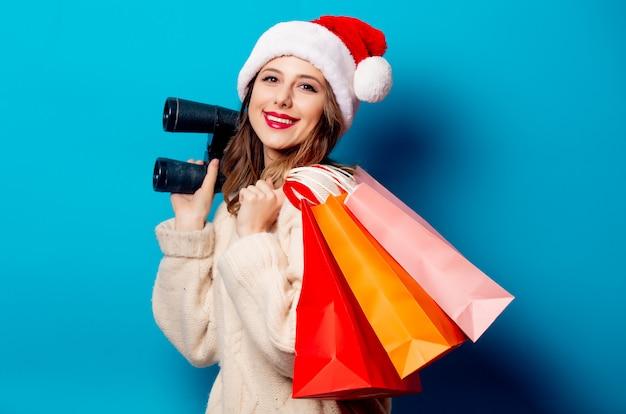 Bella donna con i sacchetti della spesa e binocolo sulla parete blu