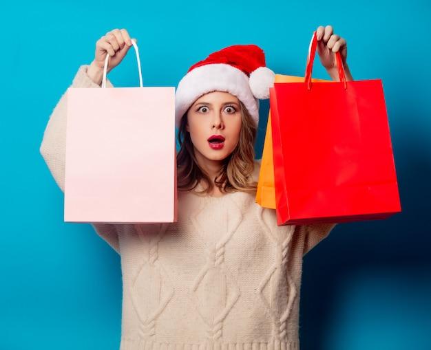 Bella donna con i sacchetti della spesa sulla parete blu