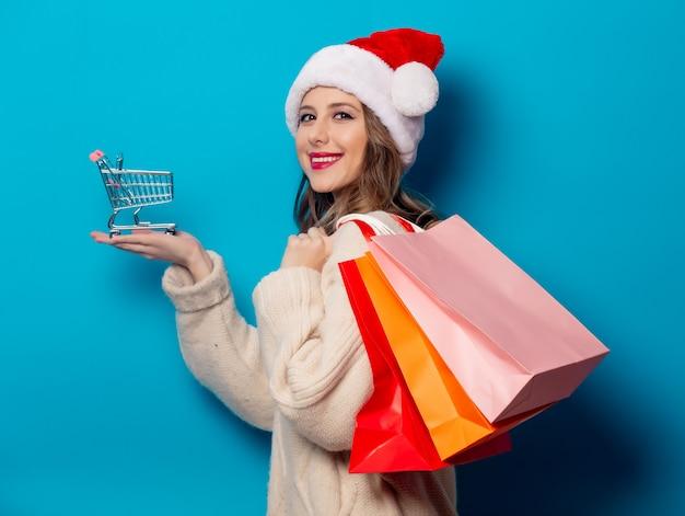 Bella donna con i sacchetti della spesa e carrello sulla parete blu