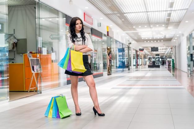 Bella donna con le borse della spesa in piedi nel centro commerciale