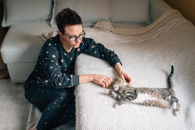 Bella donna con taglio di capelli corto si siede vicino al divano con il suo adorabile gatto