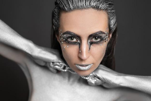 Bella donna con vernice argentata sulla pelle e sui capelli rompe la catena intorno al collo.